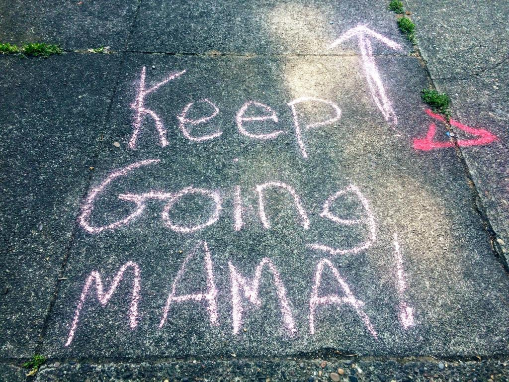 """""""Keem Going Mama!""""  with and arrow point forward written on the pavement in pink chalk."""
