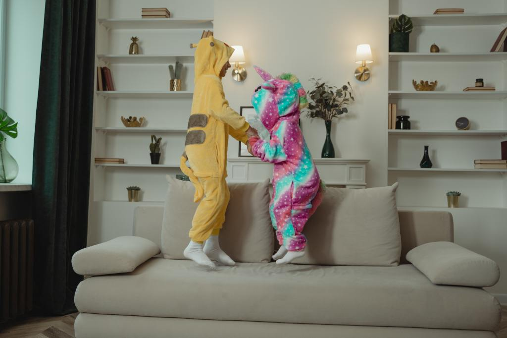 Two kids in halloween constumes jumping on a living room couch whole facing eachother and holding hands.