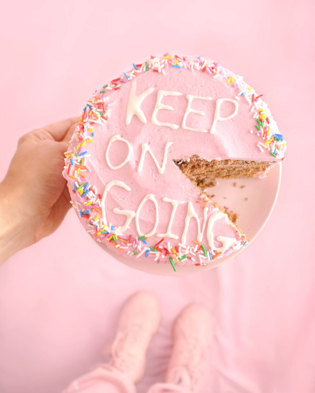 "Overhead shot of a person in pink holding a pink cake  with spinkles and the words ""Keep On Going"" written in white icing."