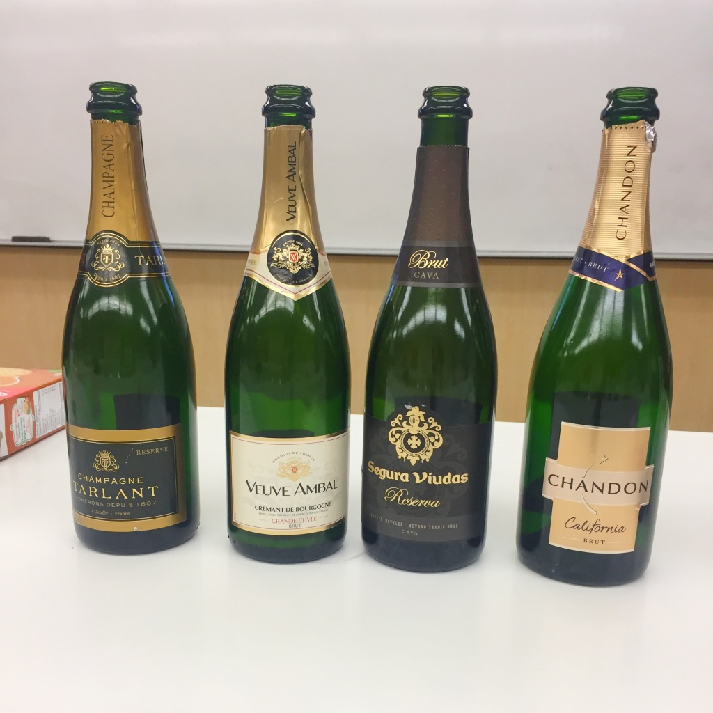 4 bottles of sparkling wine on a white countertop.