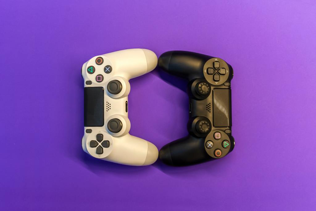 Two Playstation controlers on a purple background.