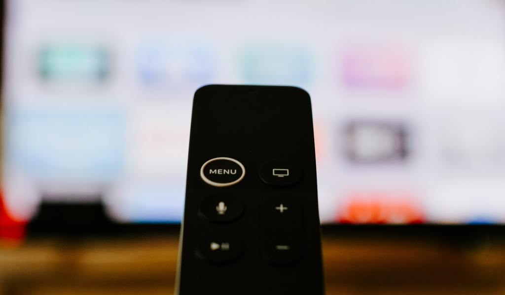 A black remote being held in front of a tv screen.