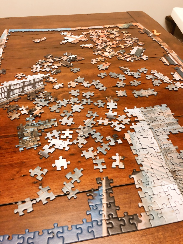 1/4 of a puzzle done on a wooden dining table.